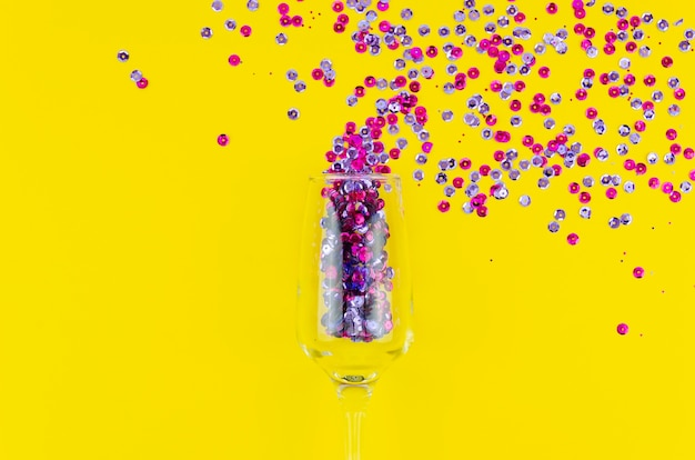 Top view colourful sequins in a wine glass