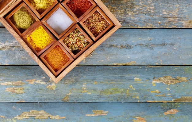 Top view of colourful spices seasonings in wooden box.