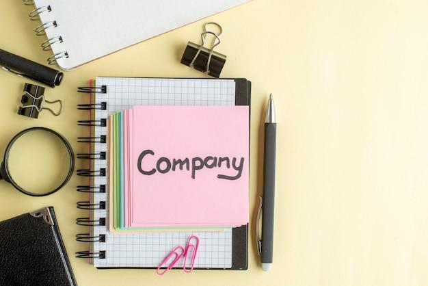 Vista dall'alto azienda nota scritta insieme a piccole note di carta colorate su superficie chiara blocco note lavoro penna scuola ufficio affari soldi colore lavoro quaderno