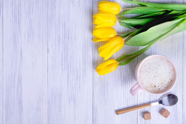 Top view of a composition of a bouquet of yellow tulips, a pink cup with cappuccino with a spoon and sugar on a light wood background.
