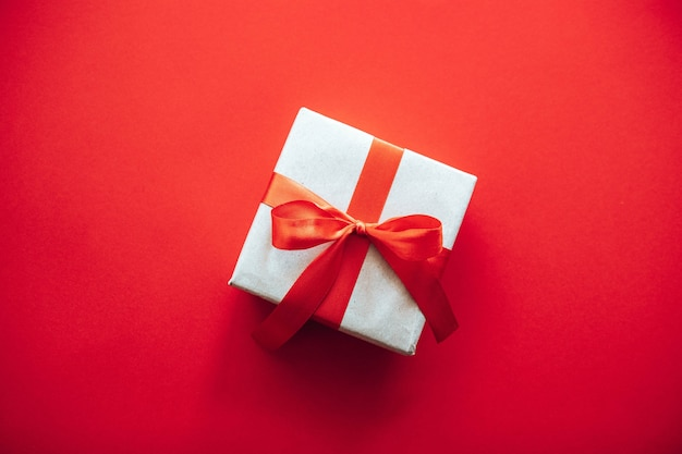 Top view composition of christmas gift box wrapped in craft paper with red ribbon bow