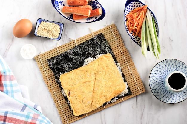 キムパプ(キムパプ)の材料、白い大理石のテーブルの上の韓国のライスロールの上面図の構成。卵、卵と海苔の入ったご飯、にんじん、ソーセージ、きゅうり、ごま、ごまソース、カニカマ