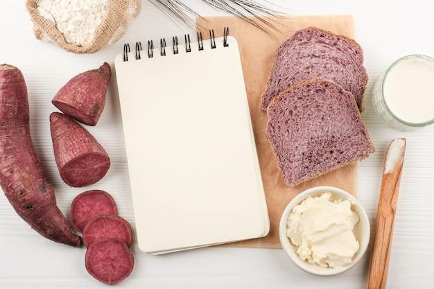 자연 색상으로 일본 보라색 고구마로 만든 슬라이스 수제 보라색 빵의 상위 뷰 구성. 건강한 다이어트 빵집에 대한 개념, 흰색 배경에 텍스트 또는 레시피 복사 공간