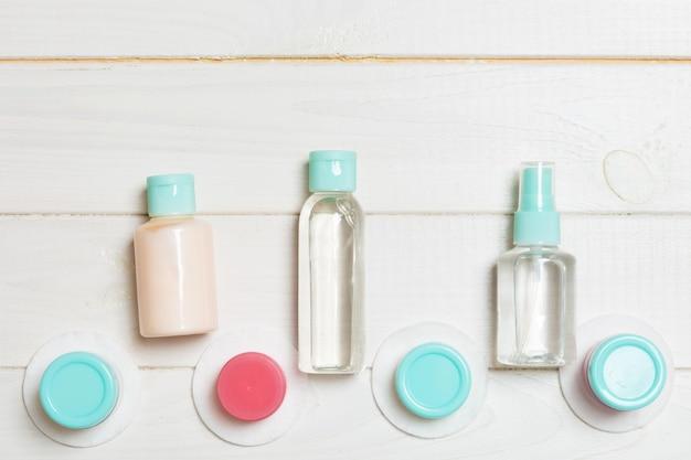 小さな旅行ボトルと木製の化粧品の瓶の平面図構成