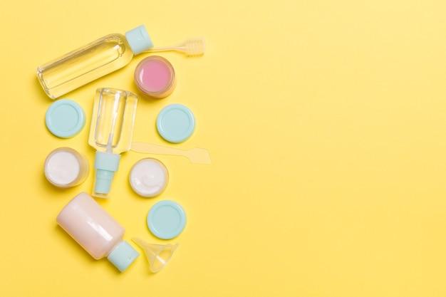 노란색 배경에 있는 화장품용 작은 여행용 병과 항아리의 상위 뷰 구성. 디자인을 위한 복사 공간이 있는 얼굴 피부 관리 개념.