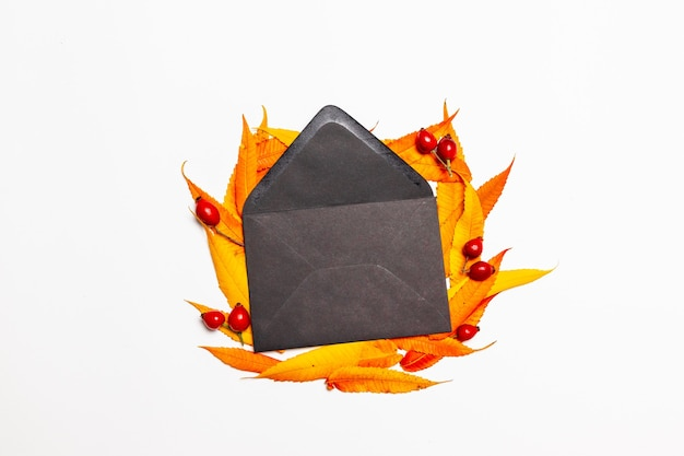 Top view composition of opened paper envelope with yellow red leaves