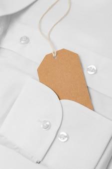 Composizione vista dall'alto dell'etichetta di imballaggio riciclabile sulla camicia bianca