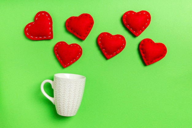 Top view composition of red hearts falling out from a cup