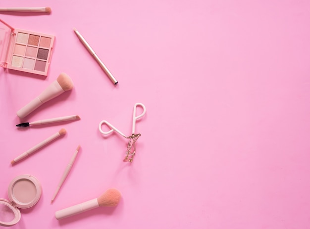 Top view composition set for professional makeup on pink background.