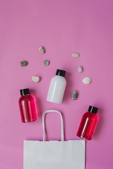 Top view composition of small travel bottles for cosmetics, shower gel, shampoo and hair balm and sea pebbles.