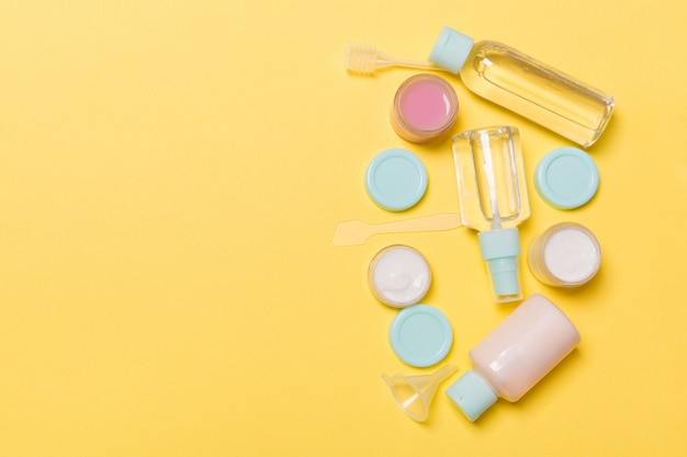 Top view composition of small travelling bottles and jars for cosmetic products on yellow background