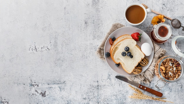 Top view composition of tasty breakfast goodies with copy space