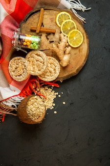 Top view of composition with corn diet bread candies cinnamon sticks lemon slices and ginger on a wooden board on black