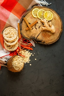 Top view of composition with corn diet bread with cinnamon sticks lemon slices and ginger on black