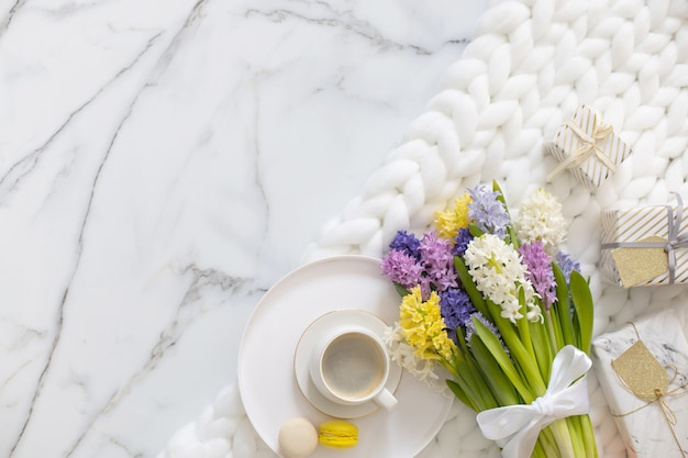 Top view composition with cup of coffee pastry macarons and spring multicolored hyacinth on white fluffy knitted plaid