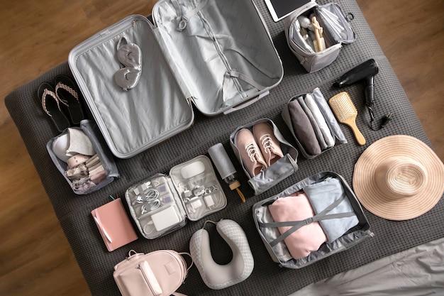 Композиция вида сверху с аккуратно упакованными вещами, одеждой и аксессуарами для путешествий методом конмари