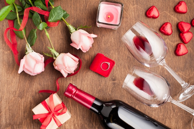 Top view composition with wine bottle and engagement ring