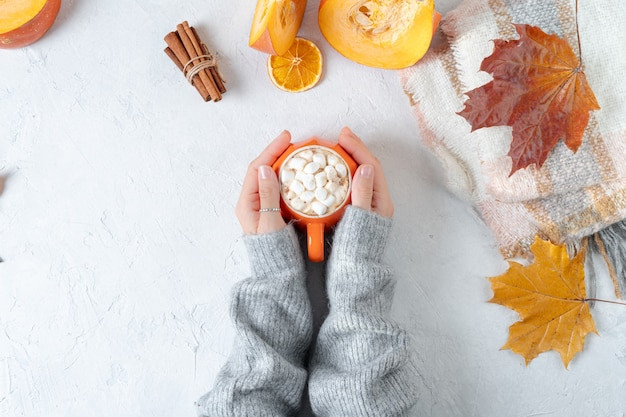 Top view composition with woman's hands in sweater and autumn decoration.
