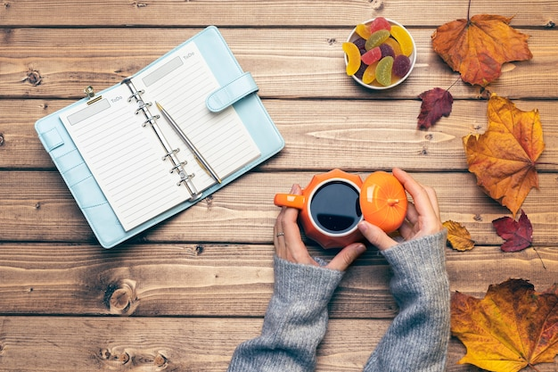 Top view composition with womans hands in sweater pumpkin styled cup of coffee and autumn themed