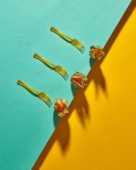 Композиция вида сверху с желтым растением физалис и вилками на желто-зеленом фоне по диагонали дуотонами с мягкими тенями. современный стиль.