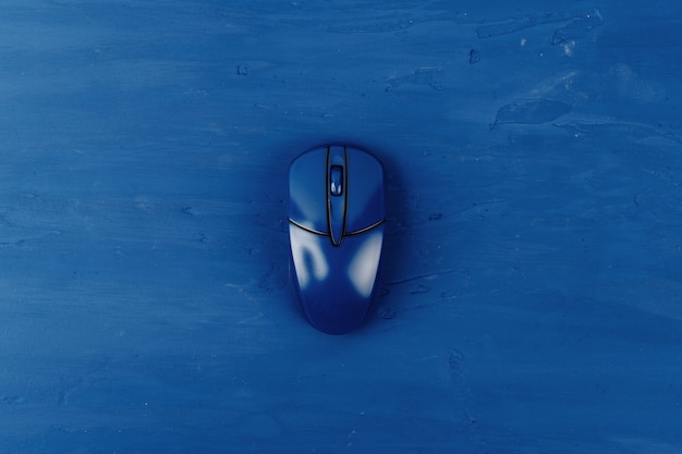 Top view of a computer mouse on classic blue color