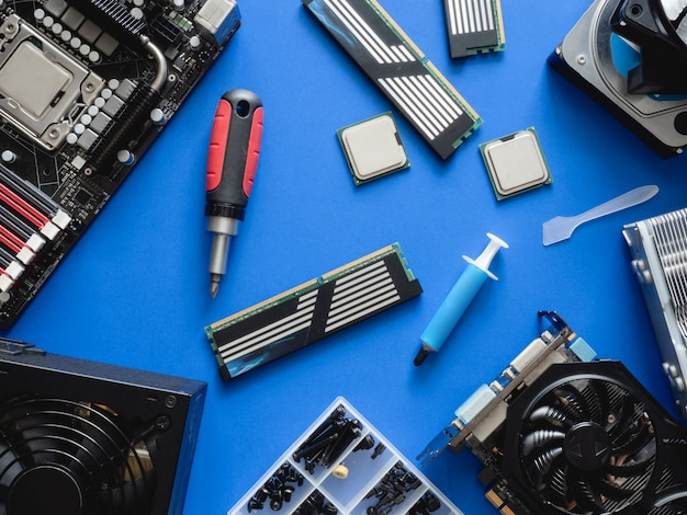 Top view of computer parts with harddisk, ram, cpu, graphics card, and motherboard on blue table background.