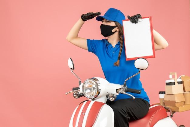 Vista dall'alto della ragazza del corriere concentrato che indossa maschera medica e guanti seduto su uno scooter con un foglio di carta vuoto che consegna ordini su sfondo color pesca pastello