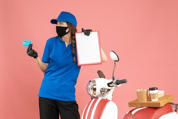 Vista dall'alto della ragazza del corriere concentrato che indossa guanti per maschera medica in piedi accanto alla moto con una torta di caffè su di essa con documenti carta di credito su sfondo color pesca pastello