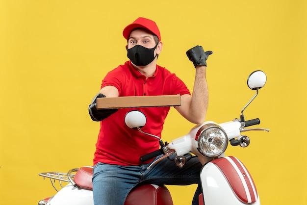 Vista dall'alto del corriere concentrato uomo che indossa camicetta rossa e guanti cappello nella mascherina medica che si siede sullo scooter che mostra l'ordine che indica indietro