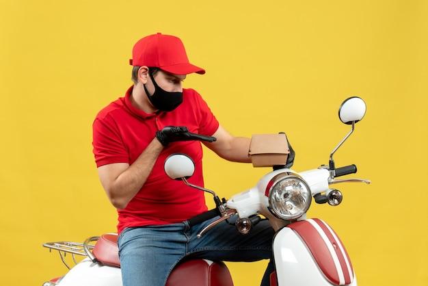 Vista dall'alto del ragazzo delle consegne concentrato indossando guanti uniformi e cappello in maschera medica che si siede sullo scooter che mostra l'ordine