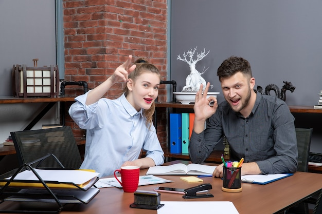 Vista dall'alto di lavoratori qualificati concentrati e motivati che fanno brainstorming su un problema in ufficio