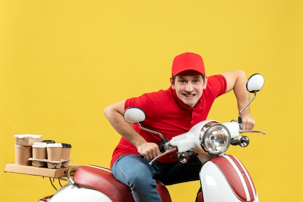 Top view of concentrated young adult wearing red blouse and hat delivering orders on yellow background