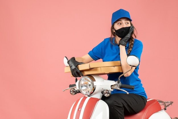 Top view of concerned female courier wearing medical mask and gloves sitting on scooter delivering orders on pastel peach background
