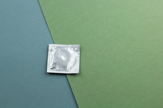 Top view condom on a blue green background copy space