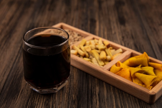 Top view of cone shape bugles chips on a wooden divided plate with a glass of cola on a wooden wall