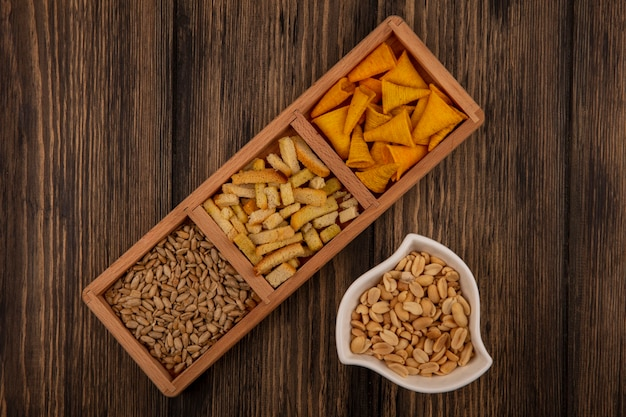 Top view of cone shape bugles chips on a wooden divided plate with shelled sunflower seeds with pine nuts on a bowl on a wooden wall