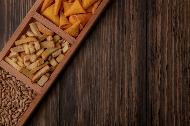 Top view of cone shape bugles chips on a wooden divided plate with shelled sunflower seeds on a wooden wall with copy space