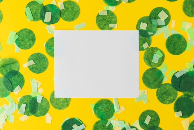 Top view of confetti frame on yellow background with copy space