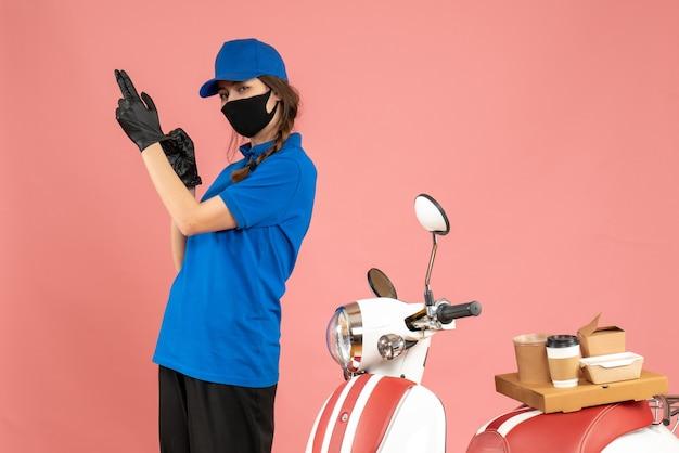 Vista dall'alto del corriere fiducioso che indossa guanti con maschera medica in piedi accanto alla moto con una torta di caffè su di esso su sfondo color pesca pastello