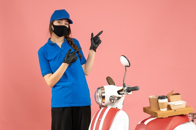 Vista dall'alto del corriere fiducioso che indossa guanti con maschera medica in piedi accanto alla motocicletta con una torta di caffè su di esso rivolta verso l'alto su sfondo color pesca pastello