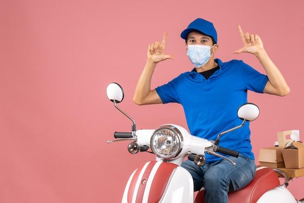 Vista dall'alto del corriere fiducioso in maschera medica che indossa un cappello seduto su uno scooter che consegna ordini su sfondo color pesca pastello