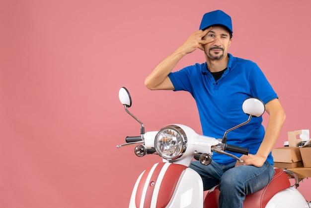 Vista dall'alto di un corriere fiducioso che indossa un cappello seduto su uno scooter che consegna ordini su sfondo color pesca pastello