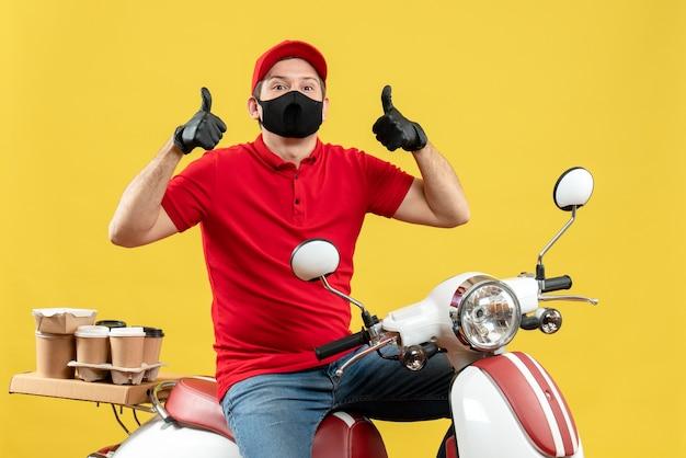 Vista superiore del ragazzo fiducioso del corriere che indossa guanti rossi della camicetta e del cappello nella mascherina medica che consegna l'ordine che si siede sullo scooter che mostra il gesto giusto