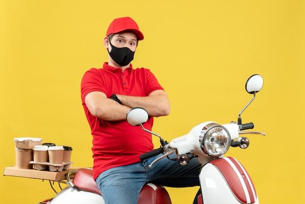 Vista superiore del ragazzo fiducioso del corriere che indossa la camicetta rossa e guanti del cappello nella mascherina medica che consegna l'ordine che si siede sullo scooter
