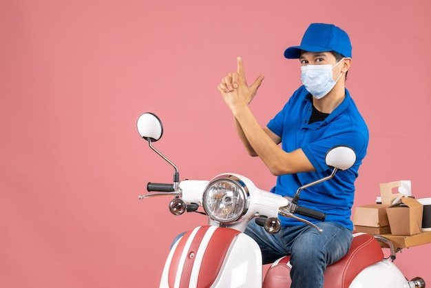 Top view of confident courier man in medical mask wearing hat sitting on scooter making gun gesture on pastel peach background