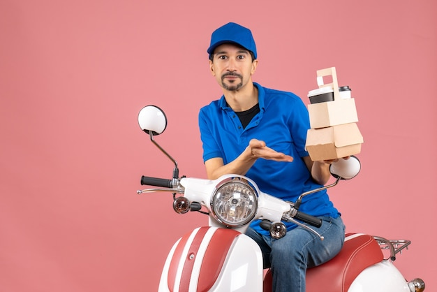 Top view of confident courier man wearing hat sitting on scooter holding orders on pastel peach background