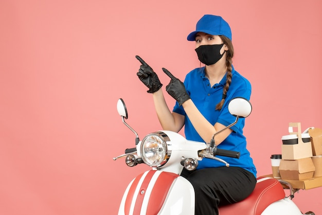 Top view of confident courier woman wearing medical mask and gloves sitting on scooter delivering orders on pastel peach background