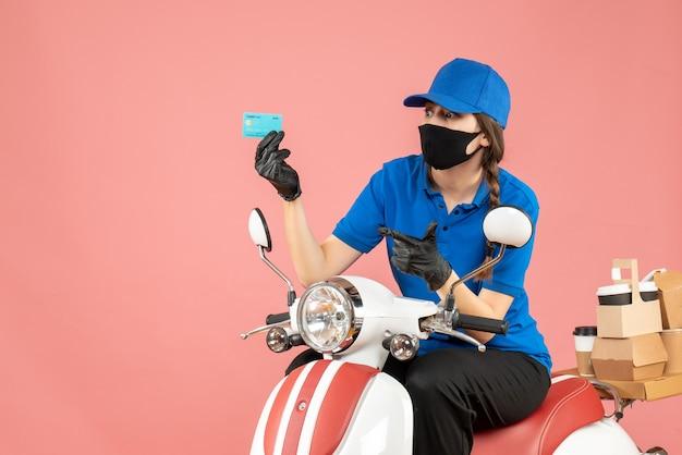 Vista dall'alto di una donna sicura del corriere che indossa maschera medica e guanti seduta su uno scooter con in mano una carta di credito che consegna ordini su sfondo color pesca pastello