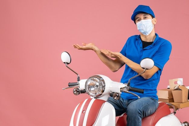 Top view of confident delivery guy in medical mask wearing hat sitting on scooter on pastel peach background