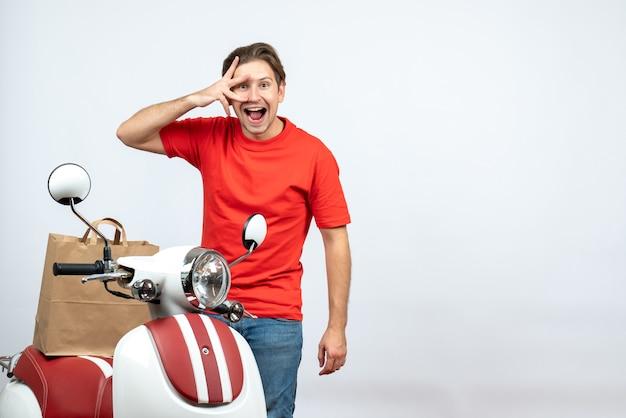 Vista dall'alto del ragazzo di consegna fiducioso in uniforme rossa in piedi vicino a scooter tenendo l'ordine su sfondo bianco